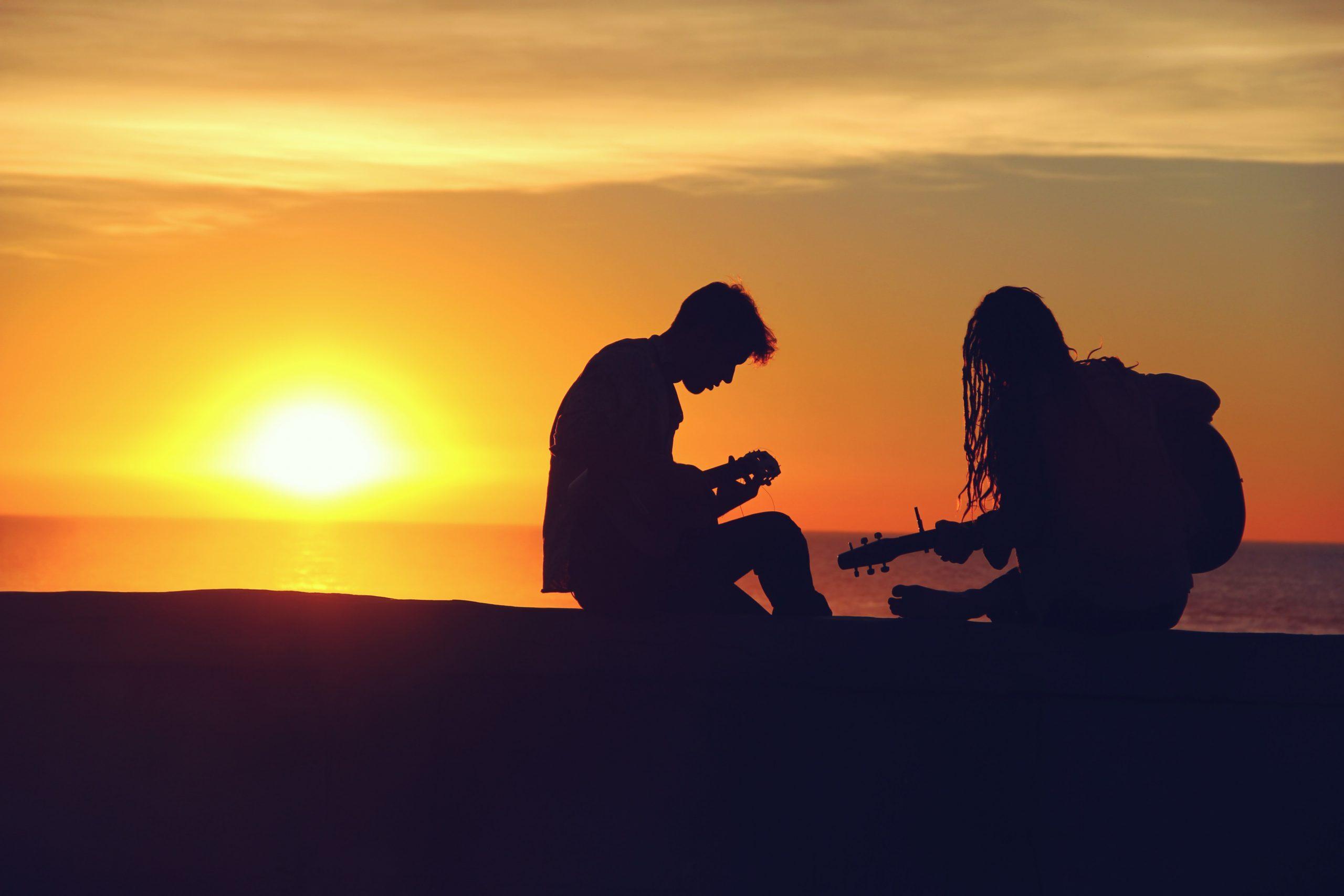 Un couple jouant de la guitare sur la plage devant un couché de soleil