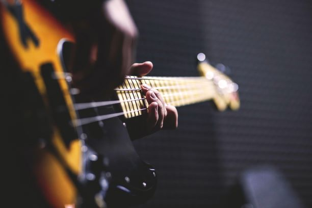 Guitare de type basse dans les mains d'un guitariste