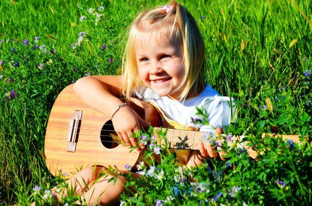 Enfant jouant avec une guitare à sa taille