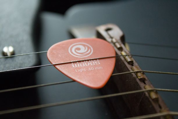 Médiator coincé entre les cordes d'une guitare